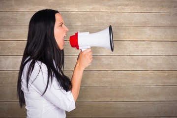 Composite image of young woman shouting through megaphone