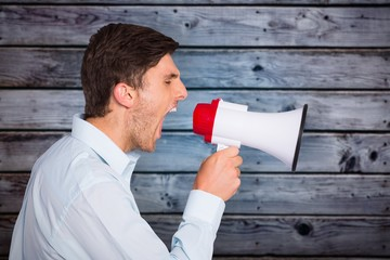Composite image of young man shouting through megaphone