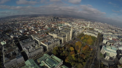 Camera flying above Vienna with a view on Rathaus and park.