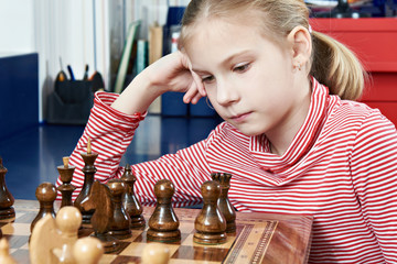Girl thinking in chess game