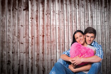 Composite image of young couple sitting on floor smiling