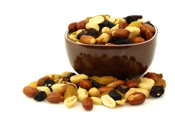 mixed peanuts and raisins in a brown bowl on a white background