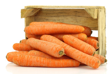 fresh winter carrots in  a wooden box on a white background