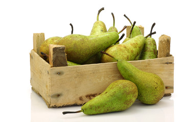 fresh juicy pears in a wooden box on a white background