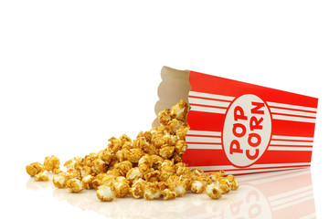 caramel popcorn in a paper popcorn cup on a white background