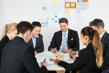 Businesspeople Analyzing Graph In Office