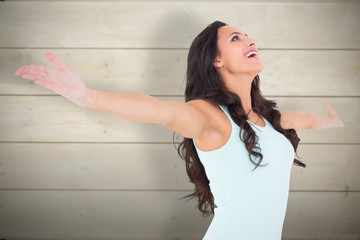 Composite image of carefree brunette with arms out