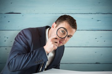 Composite image of businessman looking through magnifying glass