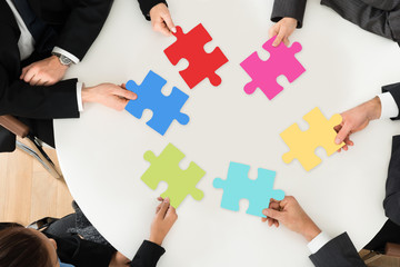 Businesspeople Holding Multi-colored Jigsaw Puzzle