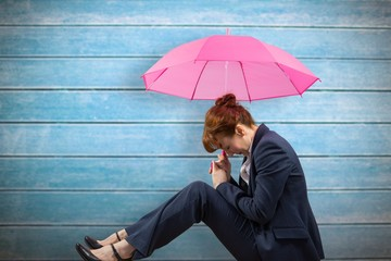 Composite image of businesswoman with umbrella