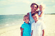 Smiling mother with children standing on the beach.