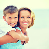 Mother and son in embrace on the beach. - Fine Art prints