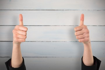 Composite image of businesswomans hands showing thumbs up