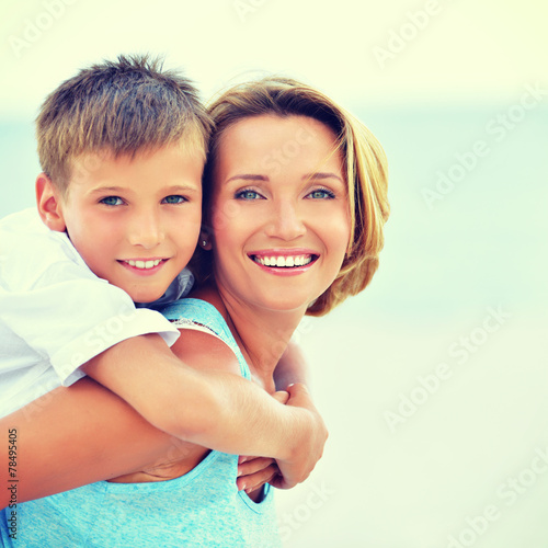 canvas print picture Mother and son in embrace on the beach.