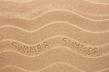 Summer inscription on the wavy sand