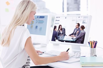 Composite image of casual young woman using computer in office