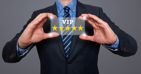 Businessman holds vip five stars in his hands. grey