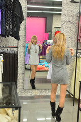 Girl tries on a new dress in the shop front of a mirror