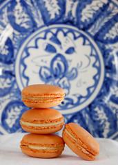 Orange macarons against a handpainted blue dish