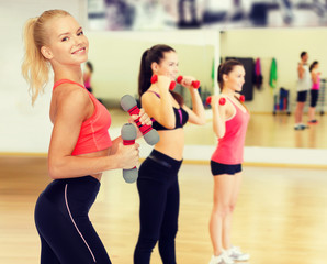 smiling beautiful sporty woman with dumbbells