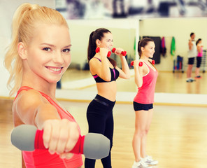 smiling beautiful sporty woman with dumbbell
