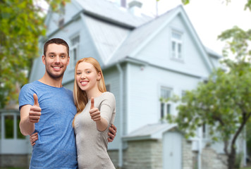 smiling couple showing thumbs up over house
