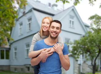 smiling couple hugging over house background