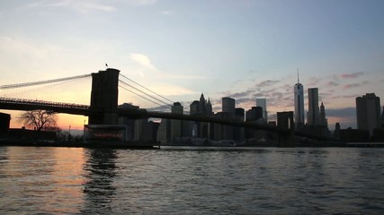 Manhattan skyline and Brooklyn bridge at sunset. Time lapse.