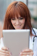 closeup portrait of smiling female doctor looking at tablet pc