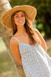 beautiful smiling girl with hat behind a tree