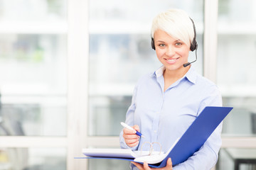 caucasian businesswoman is standing in the office with headset a
