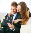 Young couple with tablet pc chatting or buying online