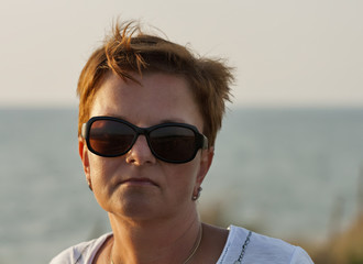 sunset portrait of tanned middle age woman in sunglasses