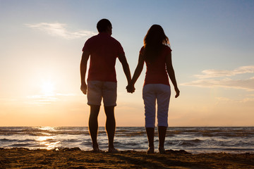 Couple Enjoying Ocean View At Beach During Sunset