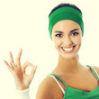 Cheerful woman in green fitness wear with okay sign