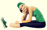Portrait of smiling young woman in green fitness wear