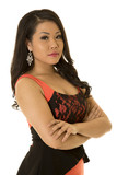 Asian woman in red dress stand arms folded serious