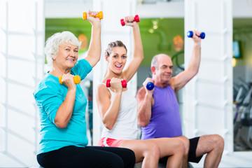 Senioren und Trainer mit Hanteln bei Fitness Sport