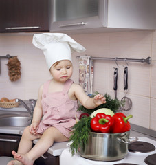 The kid in a chef's hat looking at a pot with vegetables