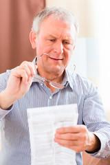 Senior liest mit Altersweitsichtigkeit Beipackzettel