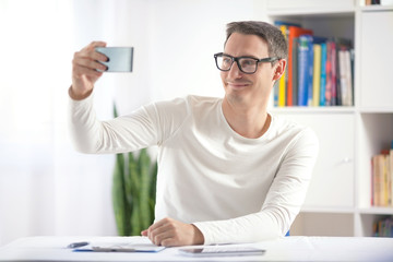 Young man taking self portrait with his mobile phone