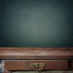 пустой деревянный стол с ящиком на фоне стены