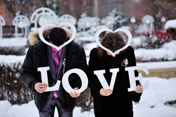 Man and woman holding letters LOVE and shape of hearts on top of