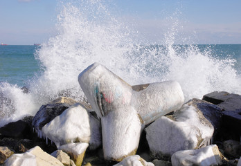 Frozen tetrapod  and waves in winter day