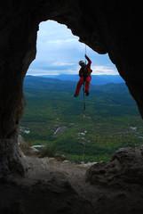 Спелеолог спускается по веревке в пещеру