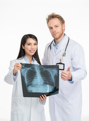 Caucasian doctor and asian female assistant discussing x-ray sca