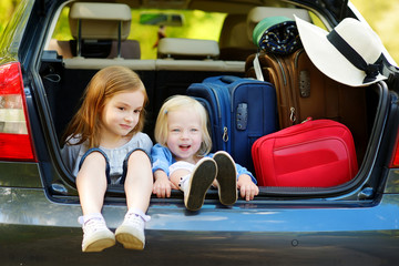 Two adorable little sisters sitting in a car