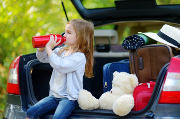 Adorable little girl drinkig water in a car
