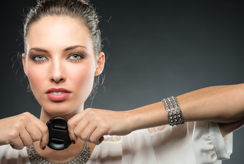 Young beautiful female photographer holding lens cap