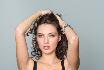 Beautiful brunette touching hair with both hands